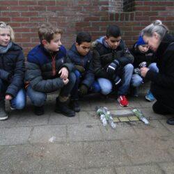 Harma Prinsen-de Vroome met schoolkinderen bij de stenen van Levie Drukker en Salomon en Henriëtte de Lange aan de Irisstraat 2 (foto Wieske Veldhuis)