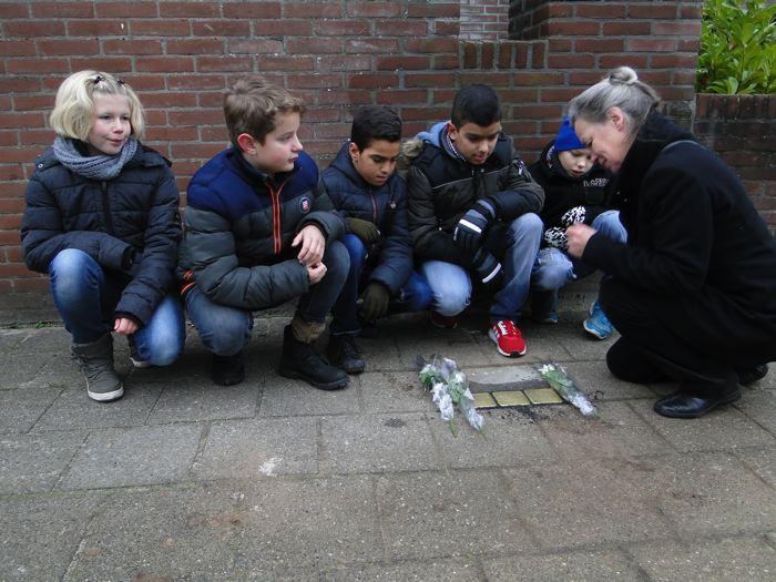 Harma Prinsen-de Vroome met schoolkinderen bij de stenen van Levie Drukker en Salomon en Henriëtte de Lange aan de Irisstraat 8 (foto Wieske Veldhuis)